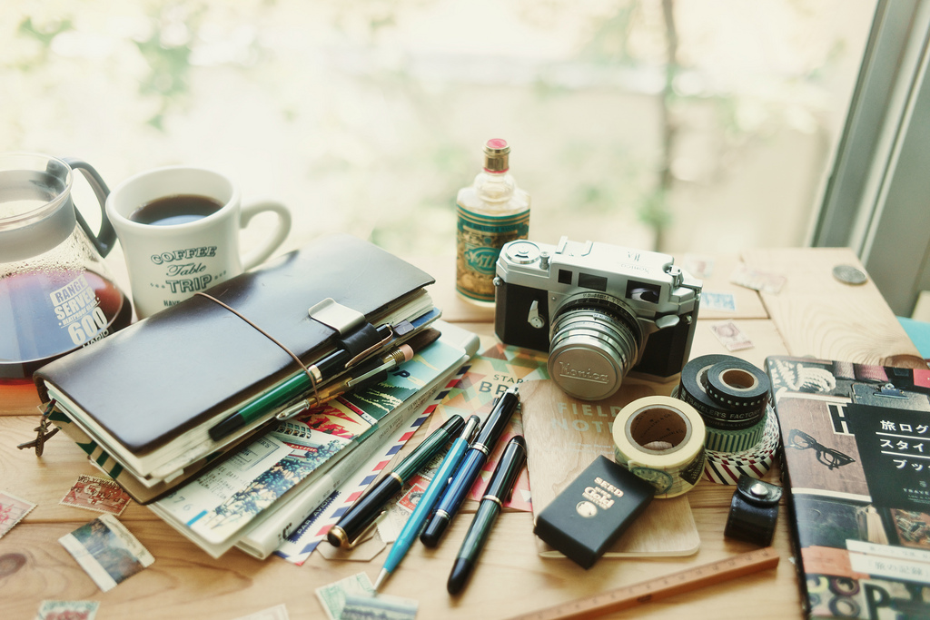 Work table with camera, notebooks, coffee, pens