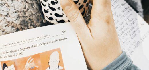 """Photo d'un bout de l'ouvrage """"(K)information"""" de Maren Klotz avec une main, des notes manuscrites et le bas d'une tasse"""